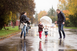 Beautiful young family with two daughters under the umbrellas, running. Walk on a rainy day.