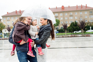 Beautiful young family with two little daughters under the umbrella, in town on a rainy day.