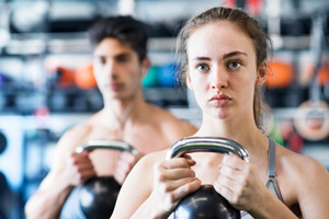 Beautiful young fit couple doing strength training, exercising with kettlebell in modern gym.