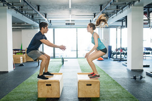 Beautiful young fit couple exercising in modern crossfit gym, doing box jumps.