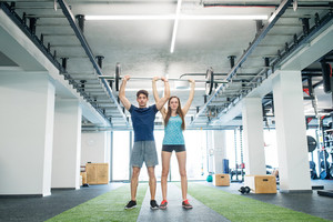 Beautiful young fit couple exercising in modern gym, lifting heavy barbell.