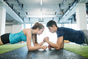 Beautiful young fit couple in modern crossfit gym doing strength training, exercising core muscles in plank position.