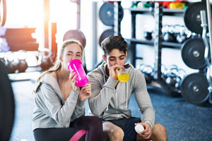 Beautiful young fit couple in modern crossfit gym resting and drinking water.