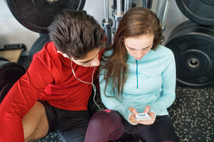 Beautiful young fit couple in modern crossfit gym resting, holding smart phone, listening music or watching something.