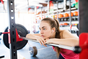 Beautiful young fit woman in gym at the heavy barbell, resting, earphones in her ears, listening music
