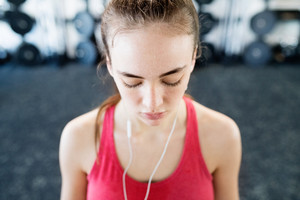 Beautiful young fit woman in gym resting, earphones in her ears, listening music