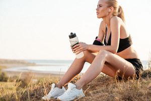 Beautiful young fitness woman relaxing after jogging and holding water bottle outdoors
