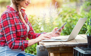 Beautiful young garden manager with smartphone and notebook working outside