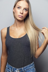 Beautiful young girl holding her blonde hair