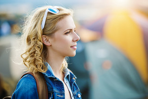 Beautiful young girl with blond curly hair at summer festival