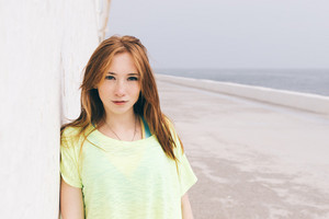 Beautiful young girl with red hair looking at camera on the beach. A woman walks along the coast on a Sunny day.