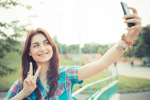 beautiful young hipster woman using smartphone in the city