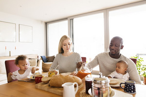 Beautiful young interracial family at home with their cute daughter and little baby son having breakfast together.