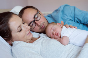 Beautiful young mother and father with their newborn baby son, lying in bed in bedroom