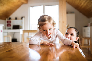 Beautiful young mother at home and her cute little daughter climbing on kitchen countertop.