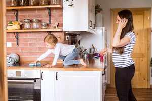 Beautiful young mother at home and her cute little daughter on kitchen countertop.