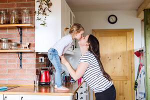 Beautiful young mother at home and her cute little daughter standing on kitchen countertop kissing her