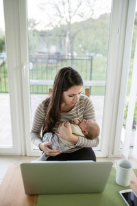 Beautiful young mother at home holding her newborn baby son, notebook and smart phone laid on table