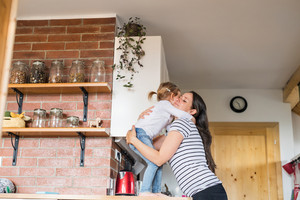 Beautiful young mother at home hugging her cute little daughter standing on kitchen countertop.