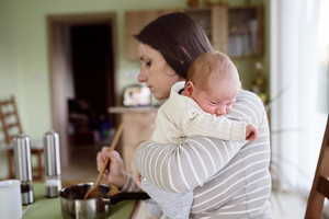 Beautiful young mother at home in the kitchen holding her newborn baby son, cooking, mixing something in pan