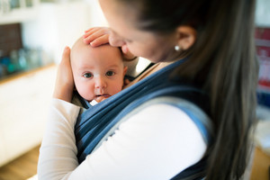 Beautiful young mother at home with her baby son in sling, stroking him gently