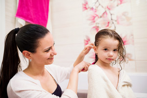 Beautiful young mother combing hair of her little daughter after taking bath