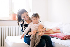 Beautiful young mother dressing her cute little daughter in the morning on a couch in living room