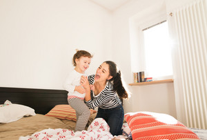 Beautiful young mother having fun with her cute little daughter on bed in her bedroom