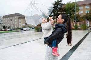 Beautiful young mother holding her little daughter under the umbrella in town on a rainy day.