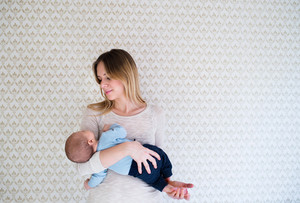 Beautiful young mother holding her sleeping baby son in her arms standing in front of wall with wallpaper on it