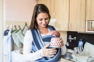 Beautiful young mother in kitchen with her newborn baby son in sling at home, holding red dotted cup