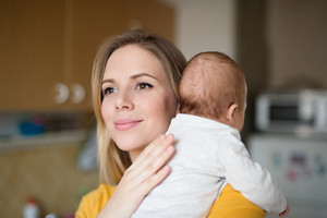 Beautiful young mother in yellow t-shirt holding her baby son in her arms