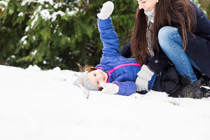 Beautiful young mother with her cute little daughter playing outside in winter nature, girl lying in the snow