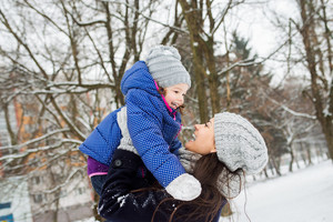 Beautiful young mother with her cute little daughter playing outside in winter nature. Mom lifting girl up.