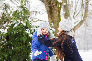 Beautiful young mother with her cute little daughter playing outside in winter nature, mother