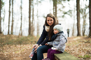 Beautiful young mother with her cute little daughter wearing warm clothes sitting on bench in autumn forest.