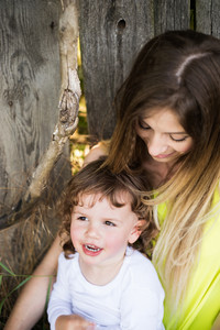 Beautiful young mother with her cute little son against old wooden fence.