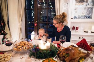Beautiful young mother with her cute little son celebrating Christmas together with their family. Food and Christmas wreath with candles laid on a table.