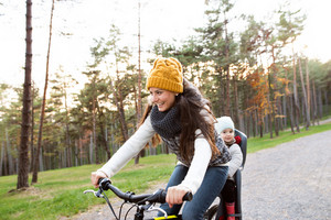 Beautiful young mother with her daughter in bicycle seat in warm clothes cycling outside in autumn nature