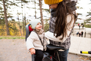 Beautiful young mother with her daughter in warm clothes on bicycle outside in autumn nature