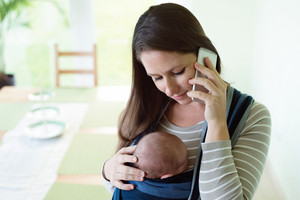 Beautiful young mother with her newborn baby son in sling at home, holding smart phone, making phone call