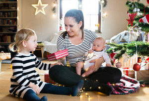 Beautiful young mother with little daughter at Christmas tree giving her Christmas present, holding her baby son in her arms.