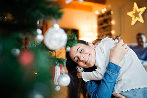 Beautiful young mother with little daughter at home decorating Christmas tree together, hugging.