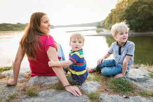 Beautiful young mother with two boys sitting and relaxing at the lake. Sunny spring day.