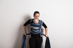 Beautiful young mother wrapping her baby son into sling. Studio shot on white background.