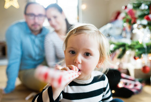 Beautiful young parents with cute daughter at Christmas tree blowing party whistle