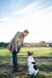 Beautiful young pregnant woman on a walk with a dog, feeding him. Green sunny nature