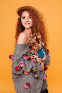 Beautiful young red hair woman carrying yorkshire terrier smiling while standing isolated on orange background
