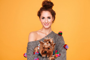 Beautiful young red head girl with cute yorkshire terrier dog isolated on orange background