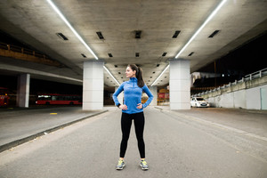 Beautiful young runner under the bridge in the town in the evening resting, arms on hips